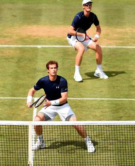 Great Britain's Andy Murray (bottom) and Jamie Murray (top) in action during day two of the Davis Cup Quarter Finals between Great Britain and France at the Queen's Club, London. Adam Davy/PA Wire.