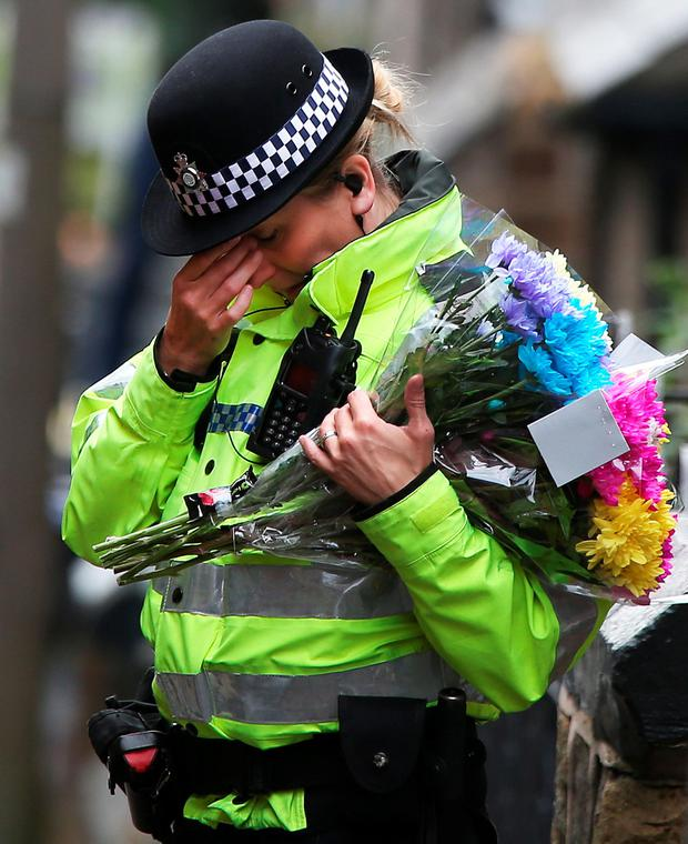 A police officer places floral tributes near a construction site on Bank End Road in Worsbrough, Barnsley, as detectives looking for Conley Thompson who vanished after playing with friends in a park have found the body of a child on a construction site.