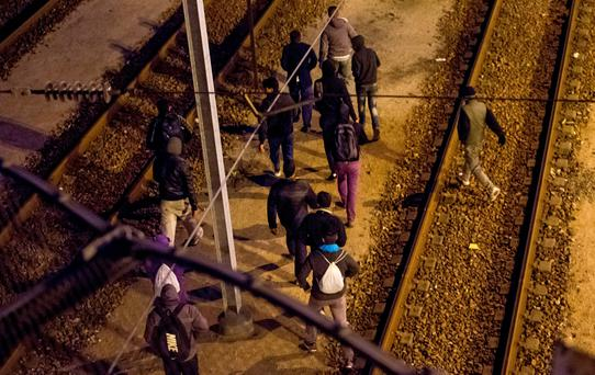 Migrants walk along railway tracks at the Eurotunnel terminal on July 28, 2015 in Calais-Frethun. Attempts by migrants desperate to reach England through the Channel Tunnel reached a new peak overnight July 27/28, as about 2,000 migrants tried to enter the Eurotunnel terminal in the French port town of Calais, northern France. AFP PHOTO / PHILIPPE HUGUENPHILIPPE HUGUEN/AFP/Getty Images