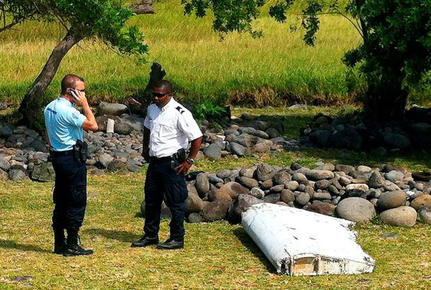A policeman and a gendarme stand next to a piece of debris from an unidentified aircraft found in the coastal area of Saint-Andre de la Reunion, in the east of the French Indian Ocean island of La Reunion, on July 29, 2015. AFP/Getty Images
