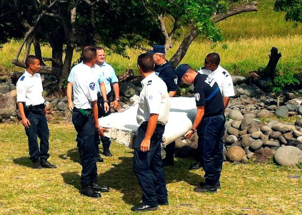 Police and gendarmes carry a piece of debris from an unidentified aircraft found in the coastal area of Saint-Andre de la Reunion, in the east of the French Indian Ocean island of La Reunion, on July 29, 2015. AFP/Getty Images