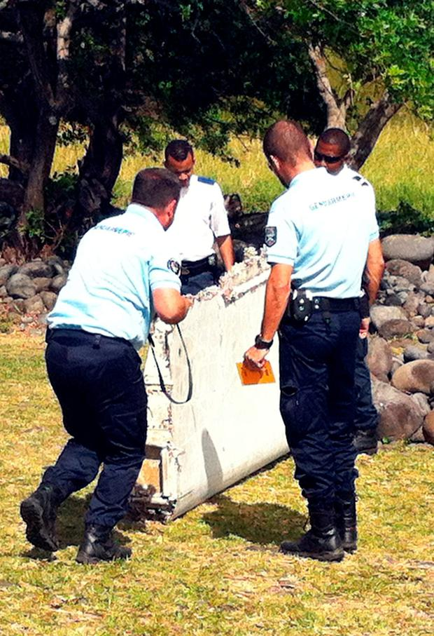 Policemen and gendarmes stand next to a piece of debris from an unidentified aircraft found in the coastal area of Saint-Andre de la Reunion, in the east of the French Indian Ocean island of La Reunion, on July 29, 2015. AFP/Getty Images