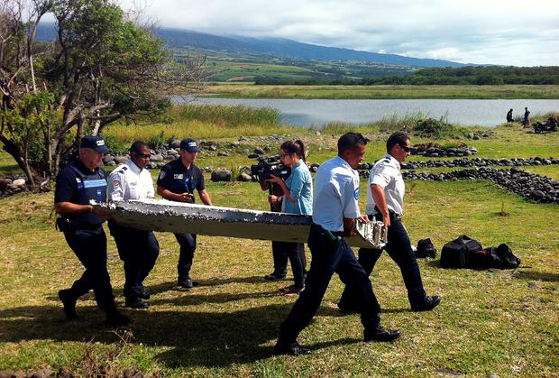 Police carry a piece of debris from an unidentified aircraft found in the coastal area of Saint-Andre de la Reunion, in the east of the French Indian Ocean island of La Reunion, on July 29, 2015. The two-metre-long debris, which appears to be a piece of a wing, was found by employees of an association cleaning the area and handed over to the air transport brigade of the French gendarmerie (BGTA), who have opened an investigation. An air safety expert did not exclude it could be a part of the Malaysia Airlines flight MH370, which went missing in the Indian Ocean on March 8, 2014. AFP PHOTO / YANNICK PITONYANNICK PITON/AFP/Getty Images