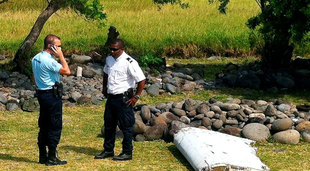 A policeman and a gendarme stand next to a piece of debris from an unidentified aircraft found in the coastal area of Saint-Andre de la Reunion, in the east of the French Indian Ocean island of La Reunion, on July 29, 2015. The two-metre-long debris, which appears to be a piece of a wing, was found by employees of an association cleaning the area and handed over to the air transport brigade of the French gendarmerie (BGTA), who have opened an investigation. An air safety expert did not exclude it could be a part of the Malaysia Airlines flight MH370, which went missing in the Indian Ocean on March 8, 2014. AFP PHOTO / YANNICK PITONYANNICK PITON/AFP/Getty Images