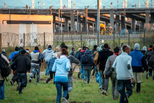 Migrants who managed to pass the police block on the Eurotunnel site run towards the boarding docks in Coquelles near Calais, northern France, on late July 29, 2015. One man died Wednesday in a desperate attempt to reach England via the Channel Tunnel as overwhelmed authorities fought off hundreds of migrants, prompting France to beef up its police presence. AFP PHOTO / PHILIPPE HUGUENPHILIPPE HUGUEN/AFP/Getty Images