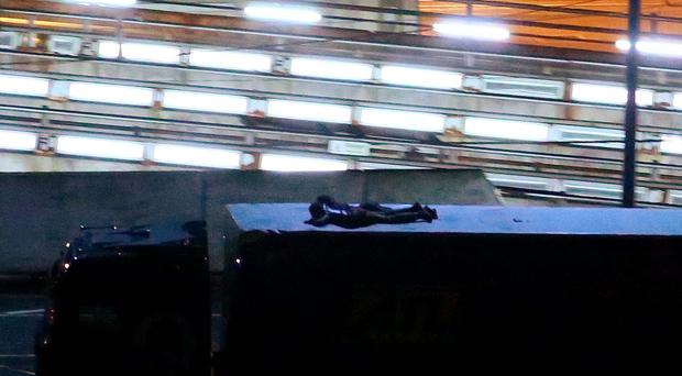 Two migrants cling to the top of a lorry as it leaves the Eurotunnel site in Folkestone, Kent, following their arrival from Calais via the Channel Tunnel. Gareth Fuller/PA Wire