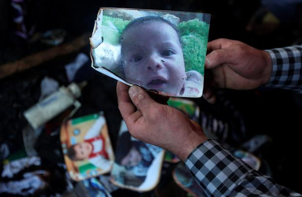 A man shows a picture of 18-month-old Palestinian toddler Ali Saad Dawabsha who died when his family house was set on fire by Jewish settlers in the West Bank village of Duma on July 31, 2015. AFP/Getty Images