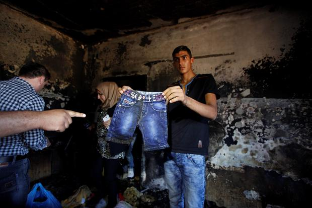 Palestinians inspect a house after it was torched in an attack by Jewish settlers killing an 18-month-old Palestinian child, his four-year-old brother and parents were wounded, according to a Palestinian official from the area. at Duma village near the West Bank city of Nablus, Friday, July 31, 2015. (AP Photo/Majdi Mohammed)