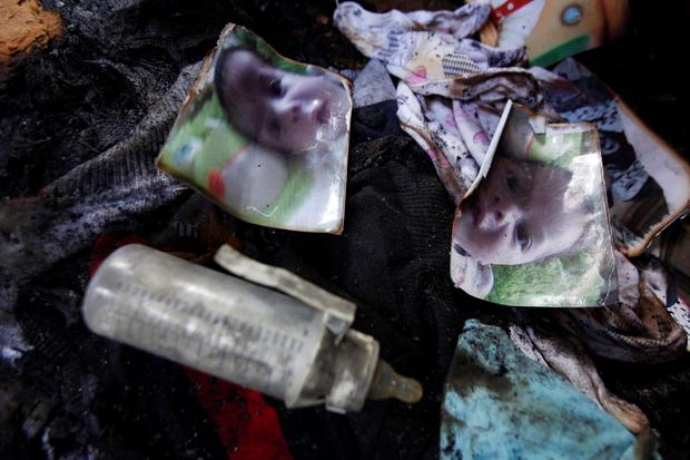 Photos of a one-and-a-half year old boy, Ali Dawabsheh, lie in a house that had been torched (AP Photo/Majdi Mohammed)