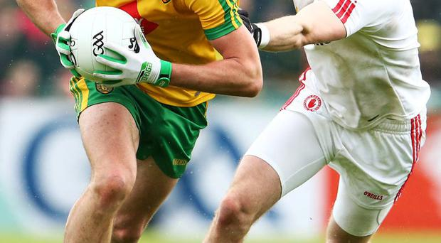 On the run: Donegal's Colm McFadden and Ronan McNamee of Tyrone clash in the Ulster Championship