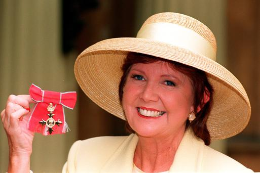 Cilla Black posing for the media with her OBE she received form the Queen during an Investiture ceremony at Buckingham Palace in London in 1997. John Stillwell/PA Wire.