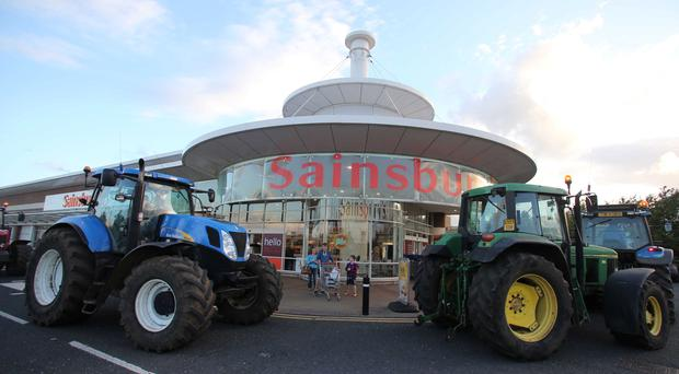 Tractors are parked outside the Sainsbury's store in Coleraine as part of a farmers' blockade of supermarkets