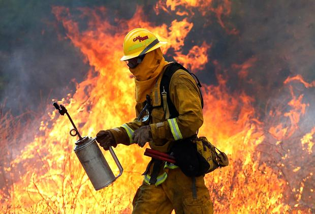 Firefighter moves away from a tall flame as he uses a drip torch to burn dry grass during a backfire operation to head off the Rocky Fire (Photo by Justin Sullivan/Getty Images)