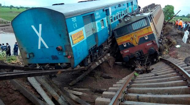 Two Indian passenger trains lay next to each other following a derailment after they were hit by flash floods on a bridge outside the town of Harda in Madhya Pradesh state on August 5, 2015. Two passenger trains derailed after being hit by flash floods on a bridge in central India, killing at least 27 people in the latest deadly accident on the nation's crumbling rail network. AFP PHOTOSTR/AFP/Getty Images
