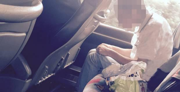 Man fills his syringe and then injects himself in the arm as shocked passengers watch