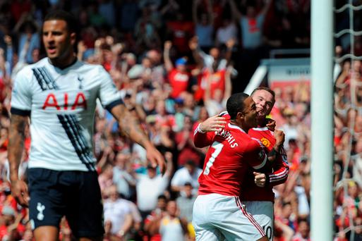 Manchester United's Dutch midfielder Memphis Depay (2nd R) celebrates with Manchester United's English striker Wayne Rooney (R) after United take the lead due to an own goal from Tottenham Hotspur's English defender Kyle Walker (L) during the English Premier League football match between Manchester United and Tottenham Hotspur at Old Trafford in Manchester, north west England, on August 8, 2015. AFP PHOTO / OLI SCARFF