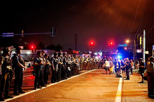 St. Louis County Police and Missouri State Highway Patrol troopers (L) stand on guard as protesters (R) march on West Florissant Avenue in Ferguson, Missouri on August 9, 2015. A day of peaceful remembrance marking the anniversary of 18-year-old black teen Michael Brown's killing by police in the US city of Ferguson came to a violent end on August 9 as gunfire left at least one protester injured. AFP PHOTO / MICHAEL B. THOMASMichael B. Thomas/AFP/Getty Images