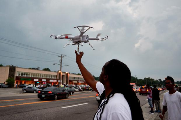 A man operates a remote control drone camera device prior to a protest march on August 9, 2015 on West Florissant Avenue in Ferguson, Missouri, marking the one year anniversary of an unarmed black teen, Michael Brown, who was shot and killed by a white police officer, throwing America's troubled race relations into harsh relief. AFP PHOTO / MICHAEL B. THOMASMichael B. Thomas/AFP/Getty Images