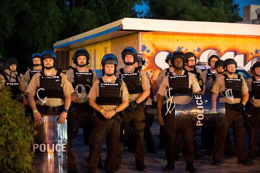 Police stand guard as demonstrators, marking the one-year anniversary of the shooting of Michael Brown, protest along West Florrisant Street on August 10, 2015 in Ferguson, Missouri. (Photo by Scott Olson/Getty Images)