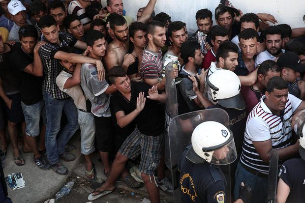 Police officers try to make space as migrants queuing for a registration procedure inside a stadium in Kos, on the Greek southeastern island of Kos, Wednesday, Aug. 12, 2015. (AP Photo/Yorgos Karahalis)
