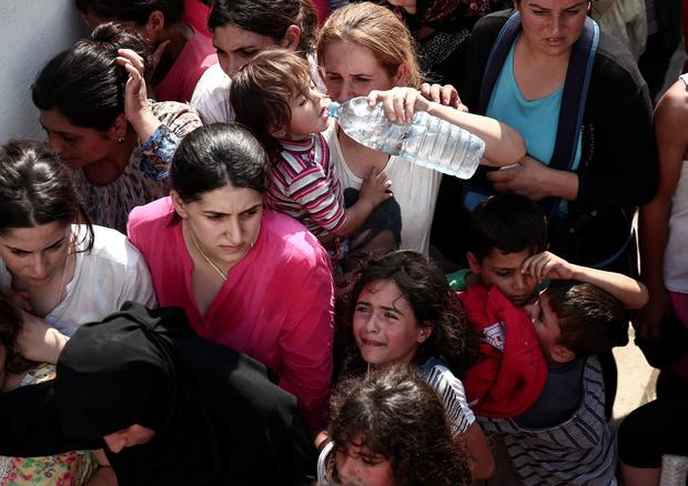 A girl cries as hundreds of migrants gather for a registration procedure at the stadium of Kos town, on the southeastern island of Kos, Greece, Tuesday, Aug. 11, 2015. (AP Photo/Yorgos Karahalis)
