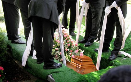 A coffin being lowered into a grave