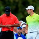 Tiger Woods and Rory McIlroy wait on the tenth tee during the final round of the 2015 Masters Tournament at Augusta