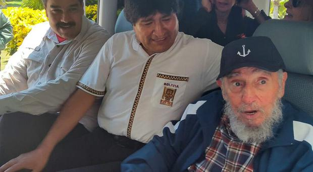 In this photo provided by the Bolivian Information Agency (ABI), Venezuela's President Nicolas Maduro, left, Bolivia's President Evo Morales, center, and Cuba's Fidel Castro, right, sit inside a van after Maduro and Castro picked up Morales at his hotel in Havana, Cuba, Thursday, 13 2015. The three leaders continued on to celebrate Castro's 89th birthday. (Ivan Maldonado/ABI via AP)