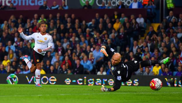 Taking aim: Memphis Depay shoots wide of the goal as Brad Guzan of Aston Villa dives in vain