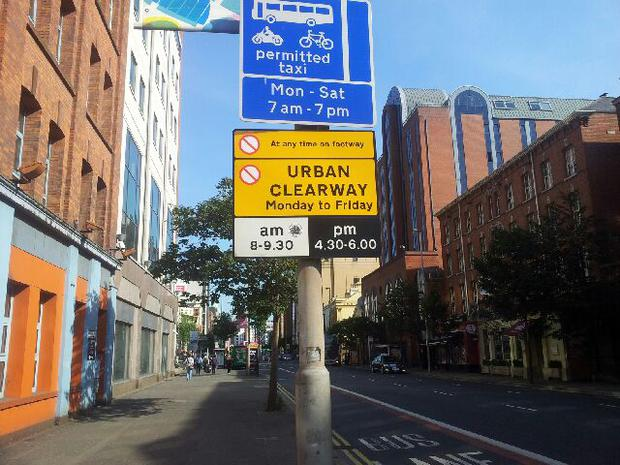 A bus lane sign placed above an urban clearway sign on Belfast's Great Victoria Street