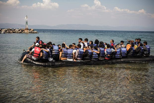 A dinghy carrying Afghan, Syrian and Iranian migrants arrives in the port of the village of Sikaminea on the Greek island of Lesbos on August 20, 2015. An unprecedented spike in refugee arrivals on Greek shores is pushing the resort island of Lesbos to