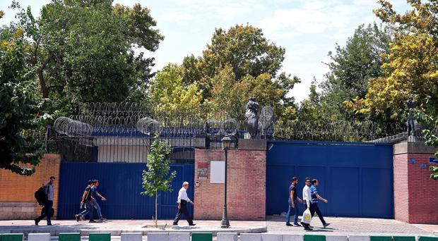 Iranian pedestrians walk past the main gate of the British Embassy in Tehran, Iran. (AP Photo/Ebrahim Noroozi)