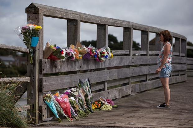 A woman lays flowers near the site where a Hawker Hunter fighter jet crashed on August 23, 2015 in Shoreham, England. The aircraft came down while performing at the Shoreham Airshow yesterday, killing at least seven people. The pilot is said to be in a critical condition in hospital. (Photo by Dan Kitwood/Getty Images) *** BESTPIX ***