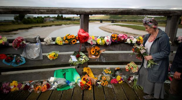 A woman carries a bunch of flowers to place on a bridge over the river Adur near where a Hawker Hunter fighter jet crashed. (Peter Macdiarmid/Getty Images)