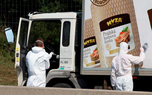 Investigators search a truck that stands on the shoulder of the highway A4 near Parndorf south of Vienna, Austria, Thursday, Aug 27, 2015. (AP Photo/Ronald Zak)