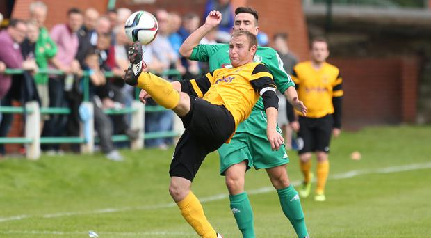 H&W Welders' William Armstrong blasts the ball clear of Dundela's Jamie Jackson