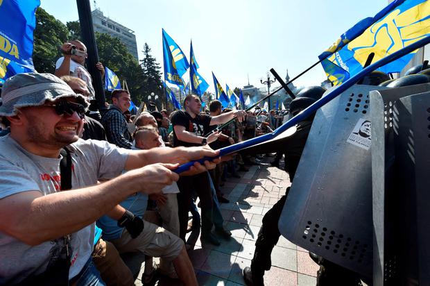 Activists of radical Ukrainian parties, including the Ukrainian nationalist party Svoboda (Freedom), clash with police officers in front of the parliament in Kiev on August 31, 2015. At least 20 were wounded in clashes outside parliament in Kiev after lawmakers gave initial approval to constitutional changes granting more autonomy to pro-Russian separatists in eastern Ukraine. A loud blast was heard outside parliament shortly after the bill was passed, an AFP journalist said. Ukrainian interior ministry advisor and top lawmaker Anton Gerashchenko wrote on Facebook that attackers threw a hand grenade at National Guard troops guarding the building in what he called an