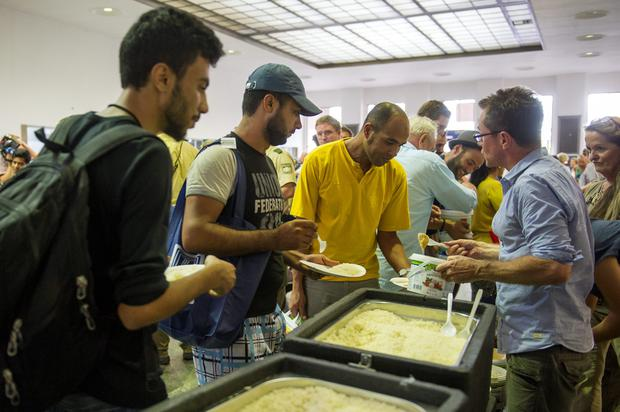 Volunteers hand over food to migrants who had arrived at Munich Hauptbahnhof main railway station on September 1, 2015 in Munich, Germany.