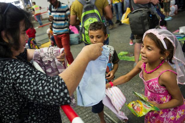 MUNICH, GERMANY - SEPTEMBER 01: A volunteer hands over clothes to migrant children who had arrived at Munich Hauptbahnhof main railway station on September 1, 2015 in Munich, Germany. Over a thousand migrants arrived in southern Germany by train in the last 24 hours, many of them who boarded trains in Budapest. According to police hundreds of migrants are arriving in southern Germany daily, either via people smugglers from Hungary along the A3 highway or via trains coming from Italy. Germany is expecting to receive 800,000 asylum-seeking migrants this year and is struggling to cope with the record number. (Photo by Lennart Preiss/Getty Images)