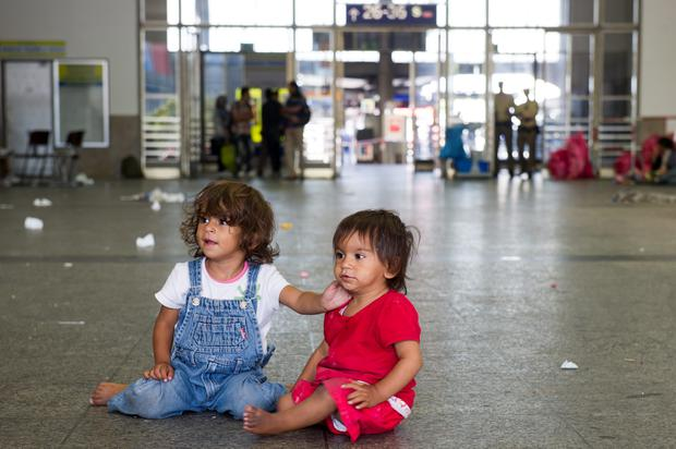 MUNICH, GERMANY - SEPTEMBER 01: Two migrant girls play on the floor of a holding area after being detained by Police at Munich Hauptbahnhof main railway station and who had no passports or valid visas on September 1, 2015 in Munich, Germany. Over a thousand migrants arrived in southern Germany by train in the last 24 hours, many of them who boarded trains in Budapest. According to police hundreds of migrants are arriving in southern Germany daily, either via people smugglers from Hungary along the A3 highway or via trains coming from Italy. Germany is expecting to receive 800,000 asylum-seeking migrants this year and is struggling to cope with the record number. (Photo by Lennart Preiss/Getty Images)