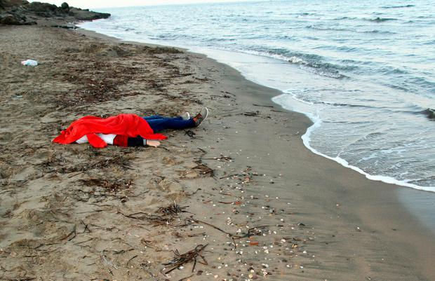 The body of a young man is covered as it lies on the shores of the city of Bodrum, in southern Turkey, after a boat carrying refugees sank as it crossed to the Greek island of Kos on September 2, 2015. AFP PHOTO/STRSTR/AFP/Getty Images