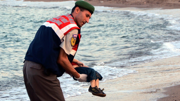 A paramilitary police officer carries the lifeless body of a child from a beach in Bodrum, Turkey, after a number of refugees died when boats carrying them to the Greek island of Kos capsized. Wednesday, Sept. 2, 2015. (AP Photo/DHA)