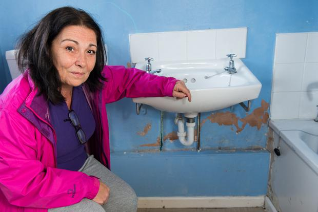Anna Fisher from Rinmore Drive in Creggan in one of the Housing Executive houses where damp is causing major problems. Pic: Martin McKeown