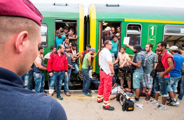A refugee receives medical attention as people protest against being taken to a refugee camp from a train that has been held at Bicske station on September 3. (Photo by Matt Cardy/Getty Images)