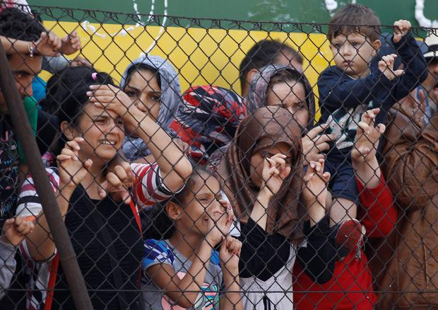 People stand behind a fence net to a train that was stopped Thursday in Bicske, Hungary, Friday, Sept. 4, 2015.AP Photo/Petr David Josek)