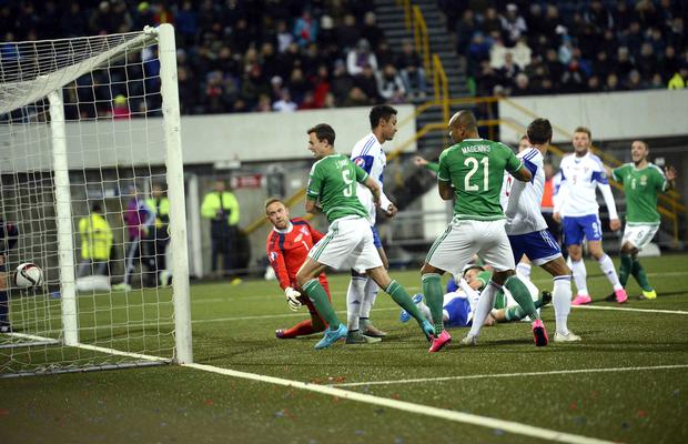 Double time: Gareth McAuley (on the ground) scores Northern Ireland's and his second goal during last night's game in the Faroe Islands