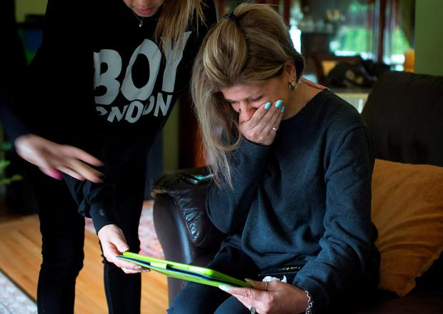 Tima Kurdi is overcome with emotion as she looks at photos of her late nephews Alan and Galib Kurdi, at her home in Coquitlam, British Columbia, Canada. (Darryl Dyck/The Canadian Press via AP)