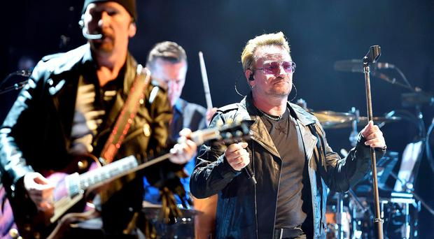 In this photo taken on Friday, Sept. 4, 2015, Bono Vox, right, leader of Irish rock band U2, performs in Turin, Italy, on the occasion of the band's opening of their European tour. (Alessandro Di Marco/ANSA via AP)
