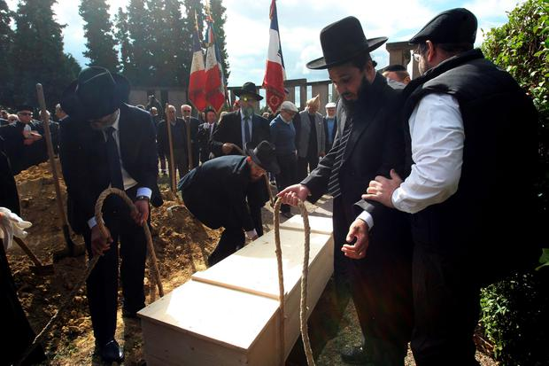 Members of the Jewish community of Strasbourg lower a coffin bearing the remains of a Jewish victim of Nazi anatomist August Hirt, during a ceremony at the Jewish cemetery of Cronenbourg, eastern France. (AP Photo/Christian Lutz)