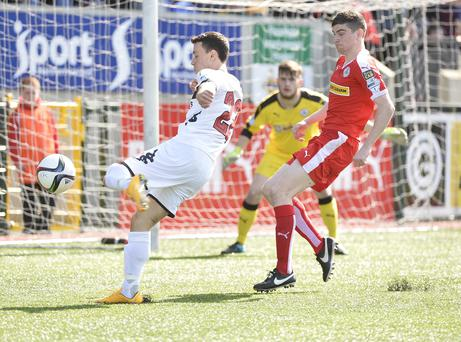 Close call: Paul Heatley of Crusaders tees up a shot under the watchful eye of Cliftonville's Caoimhin Bonnar
